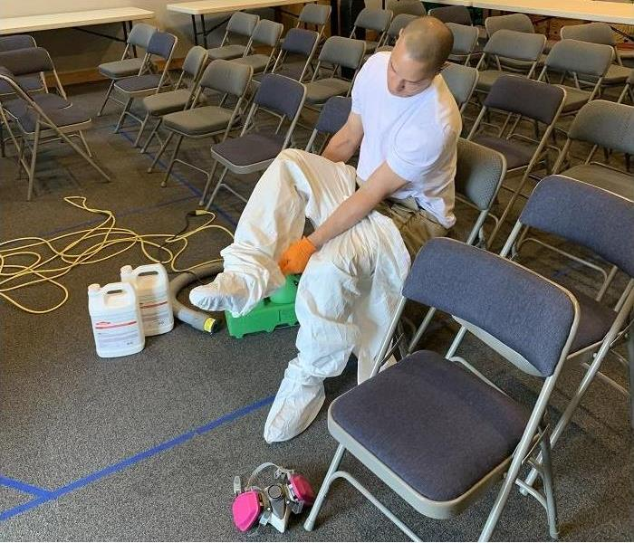 SERVPRO Tech putting on PPE to disinfect building